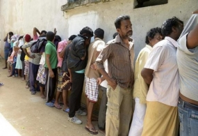Sri Lankan asylum seekers who were sent back by Australia cover their faces as they wait to enter a magistrate's court in the southern port district of Galle July 8, 2014. File Photo
