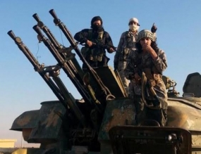 This August 7, 2014 image posted by the Raqqa Media Centre shows fighters from the Islamic State group on top of a military vehicle with anti-aircraft guns in Syria's Raqqa Province.